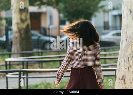 Rear view of mid adult woman strolling and carrying digital tablet in city park - Stock Photo