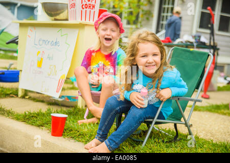 Candid portrait of two smiling girls selling lemonade and popcorn at yard sale - Stock Photo