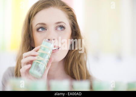 Woman smelling product from display shelf - Stock Photo