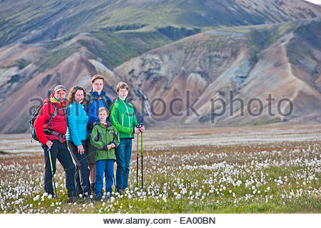 Portrait of family standing in the cottongrass meadow at Vondugil, Landmannalaugar, Fjallabak, Iceland - Stock Photo