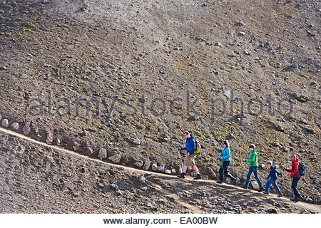 Family walking up a hill at Landmannalaugar, Fjallabak, Iceland - Stock Photo