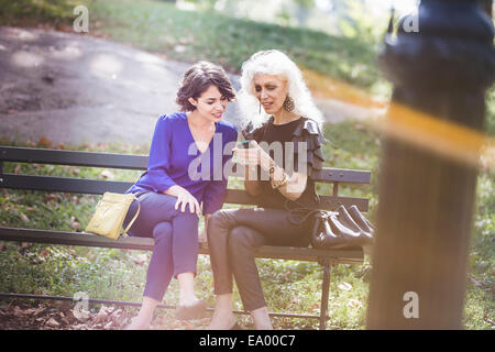 Young woman in city park with mentor looking at photos in smartphone - Stock Photo