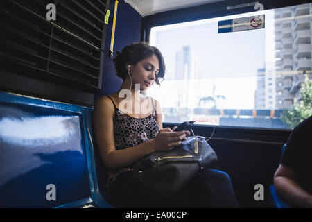 Young woman commuting on bus listening to music on smartphone, New York, US - Stock Photo