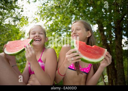 Friends eating watermelon in garden - Stock Photo