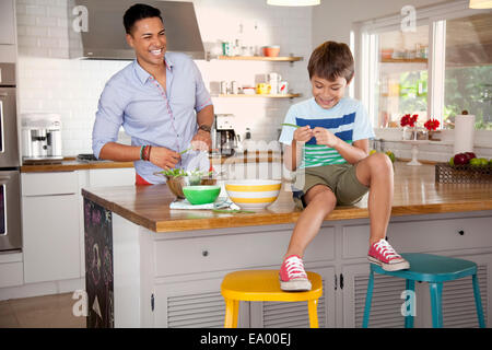 Father and son in kitchen, boy sitting on counter - Stock Photo