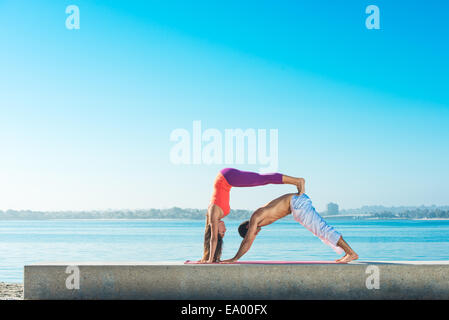 Young man and woman practicing yoga on Pacific beach, San Diego, California, USA - Stock Photo