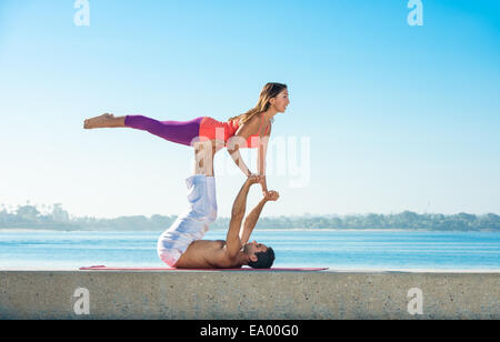 Young man and woman practicing yoga on pier at Pacific beach, San Diego, California, USA - Stock Photo