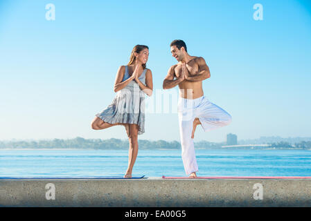 Young man and woman practicing yoga position on pier at Pacific beach, San Diego, California, USA - Stock Photo