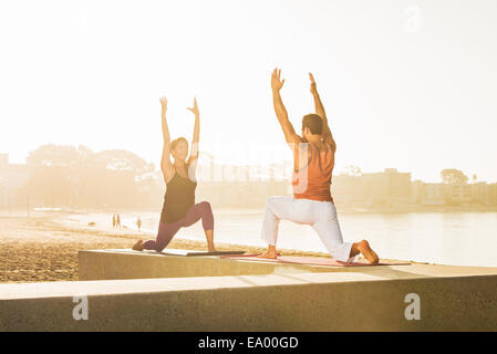 Young man and woman doing yoga on pier at Pacific beach, San Diego, California, USA - Stock Photo