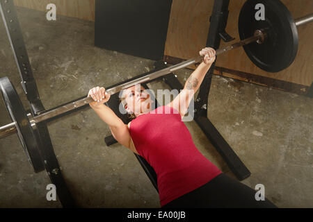 Mid adult female weightlifter lifting barbell in gym - Stock Photo