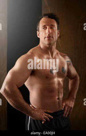 Portrait of muscular mid adult man in gym - Stock Photo
