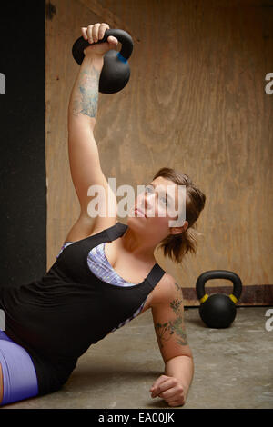 Young woman lifting kettlebell in gym - Stock Photo