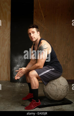Portrait of mid adult man sitting on atlas ball in gym - Stock Photo