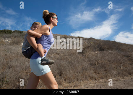 Mature woman giving son a piggy back up hill, County Park, Los Angeles, California, USA - Stock Photo
