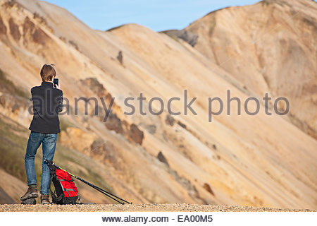 Teenager taking selfie on his smartphone at Landmannalaugar, Fjallabak, Iceland - Stock Photo