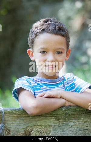 Portrait of boy leaning on garden fence - Stock Photo
