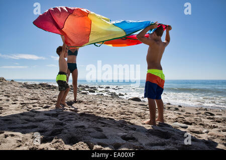 Mature woman and two sons holding up multi colored textile on beach, County Park, Los Angeles, California, USA - Stock Photo
