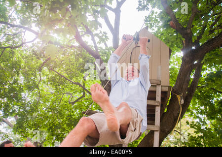 Mature man sliding down on pulley from tree house - Stock Photo