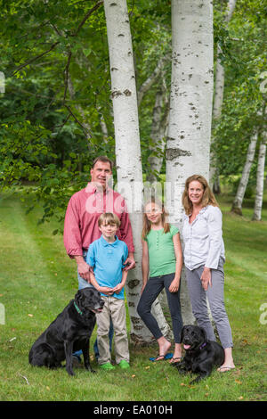 Portrait of family with two dogs - Stock Photo