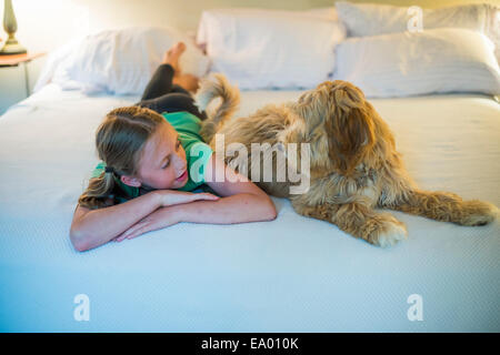 Young girl lying on bed next to dog - Stock Photo