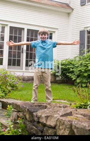 Portrait of young boy in garden, arms outstretched - Stock Photo