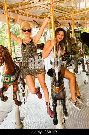 Two young women riding horse carousel in park - Stock Photo