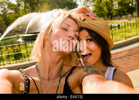 Two young women taking selfie in park - Stock Photo