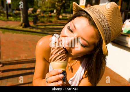 Young woman eating ice cream cone in park - Stock Photo