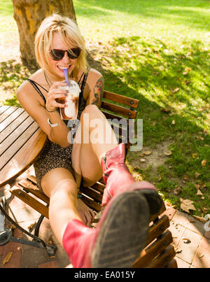 Portrait of young woman in park drinking frappe - Stock Photo