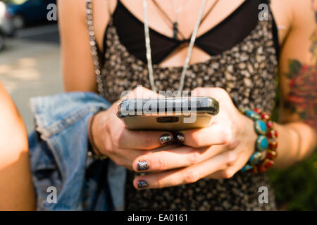 Cropped shot of young woman texting on smartphone - Stock Photo