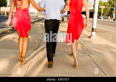 Rear cropped view of two young women arm in arm with male friend strolling on street - Stock Photo
