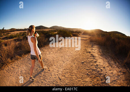 Young female jogger on path, drinking, Poway, CA, USA - Stock Photo