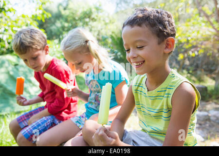 Three children in garden eating ice lollies - Stock Photo