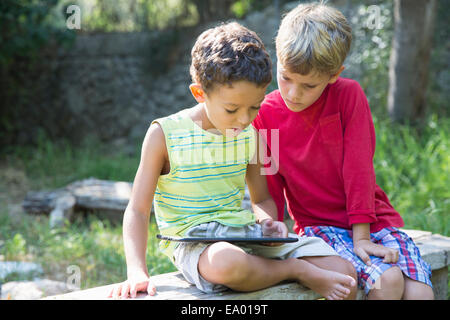 Two boys sitting on garden seat looking down at digital tablet - Stock Photo