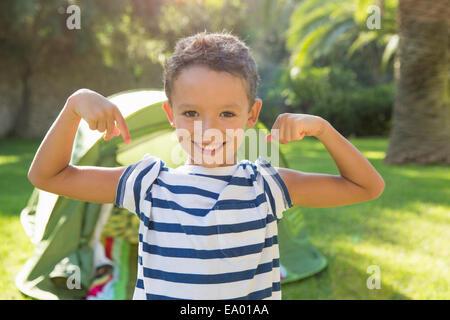 Portrait of boy in garden flexing muscles - Stock Photo
