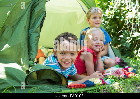 Portrait of three smiling children lying in garden tent - Stock Photo