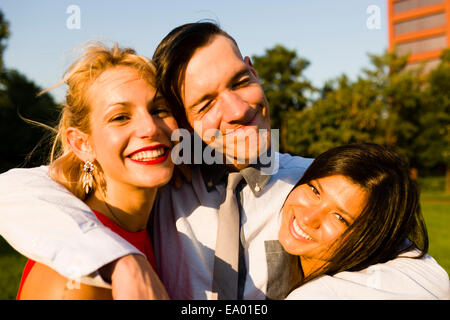 Portrait of three young adult friends hugging