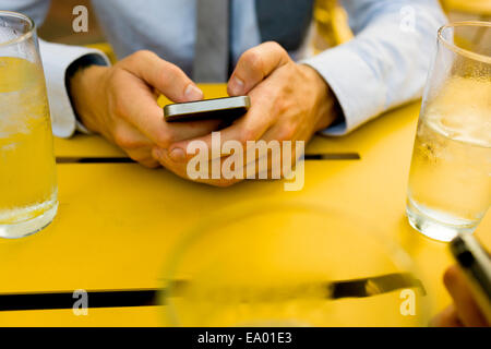 Hands of young man texting on smartphone at sidewalk cafe - Stock Photo