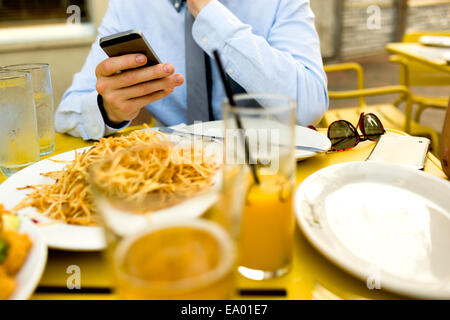 Cropped shot of young man texting on smartphone at sidewalk cafe - Stock Photo