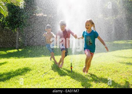Three children in garden running through water sprinkler - Stock Photo