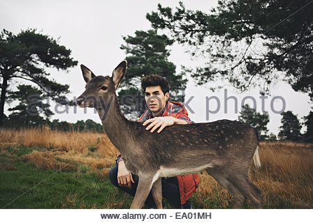 Young man crouching in field petting a deer - Stock Photo