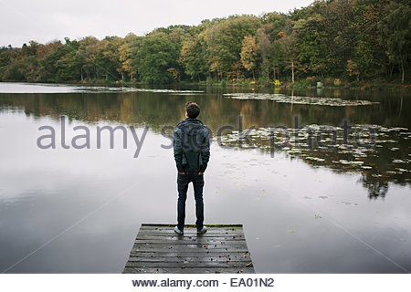 Rear view of young man standing on river pier - Stock Photo