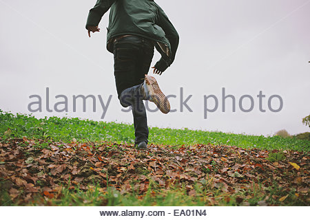 Cropped shot of young man running in field - Stock Photo