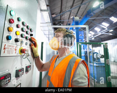 Worker at controls of metal ore grinding mill - Stock Photo