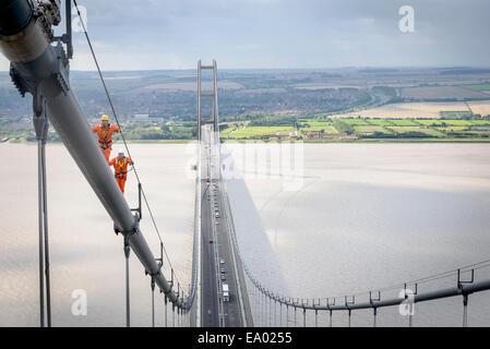 Bridge workers walking on cable of suspension bridge Humber Bridge UK was built in 1981 - Stock Photo