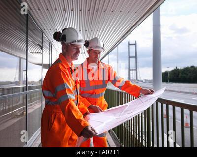 Bridge workers inspecting engineering plans for suspension bridge Humber Bridge UK was built in 1981 - Stock Photo