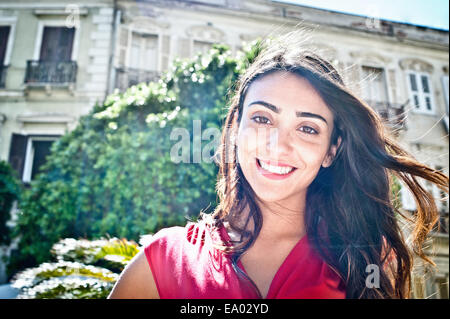 Portrait of smiling young woman on street, Cagliari, Sardinia, Italy - Stock Photo