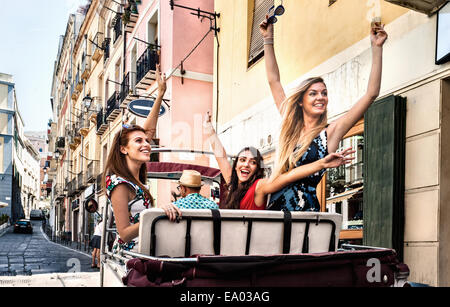 Three young women in open back seat of Italian taxi, Cagliari, Sardinia, Italy - Stock Photo