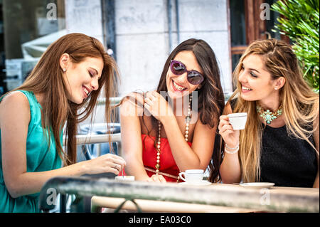 Three young female friends drinking espresso at sidewalk cafe, Cagliari, Sardinia, Italy - Stock Photo