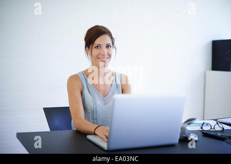 Portrait mid adult woman working from home on laptop - Stock Photo